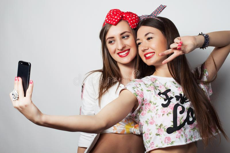Lifestyle, fashion and people concept: Two young girl friends standing together, take photo and having fun. stock images
