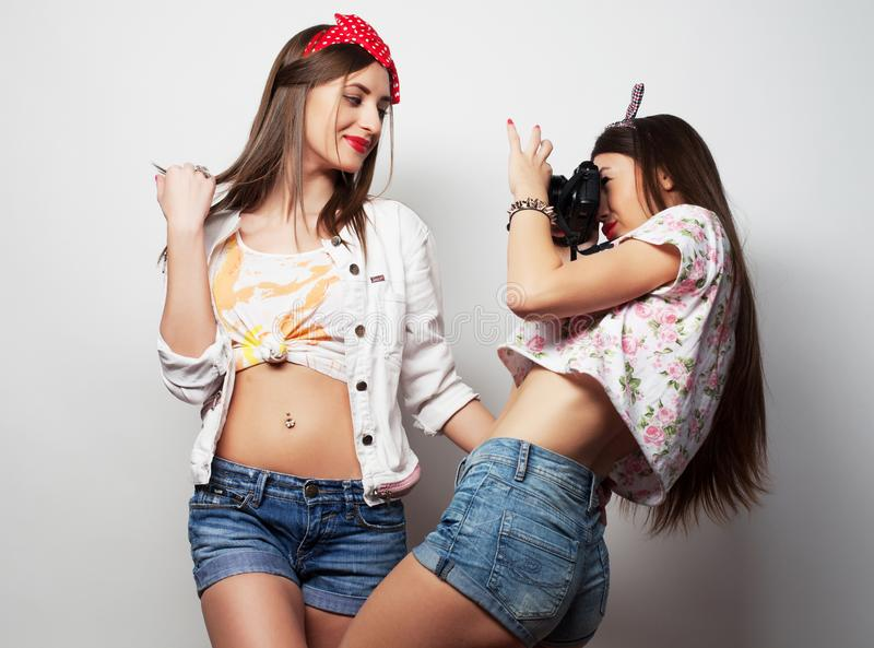 Lifestyle, fashion and people concept: Two young girl friends standing together, take photo and having fun. stock photography