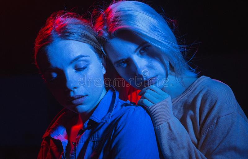 Two young girl having fun in club. Colorful portret of lesbian couple stock photo