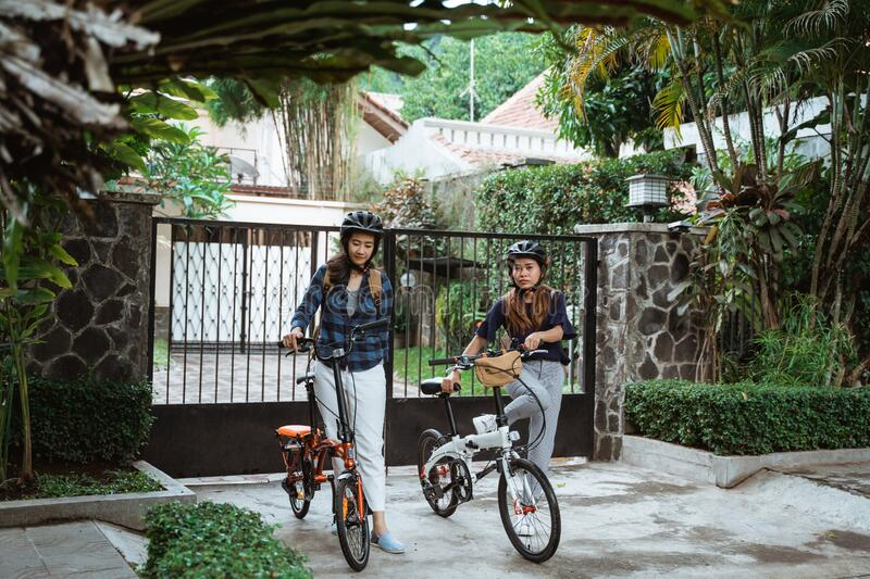 Two young girl are ready go to school by folding bicycle stock image
