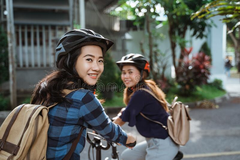 Two young girl are ready go to school by folding bicycle stock photos