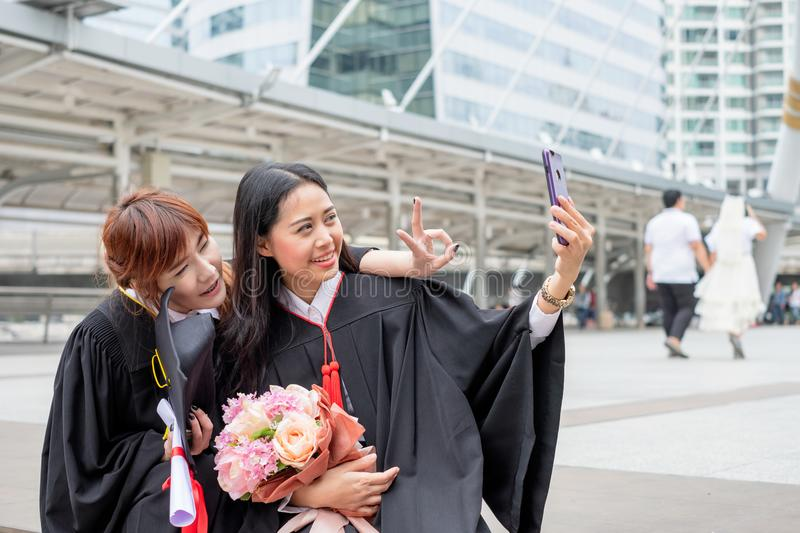 Two young girl take a photo with phone in celebration a graduation bachelor royalty free stock image
