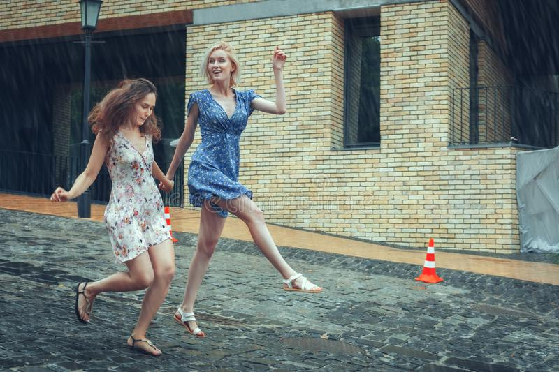 Two girlfriends having fun in the summer rain. Two young girlfriends run along the road in the summer rain royalty free stock photography
