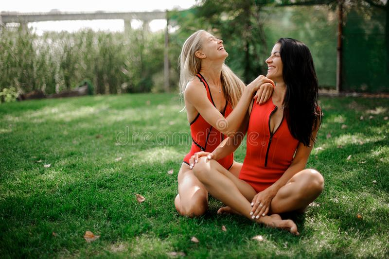 Two attractive young girls sitting on the green grass in swimsuits. Two young girls, blonde and brunette, in red swimsuits sitting on the green grass and stock photo