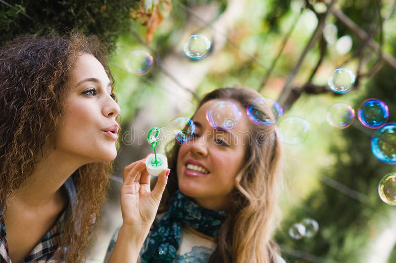 Two young girls blowing bubbles royalty free stock photos