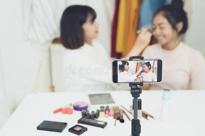 Two young girls doing video recording by smartphone camera. Asian woman make up artist applying powder on female blogger face with. Two young girls doing video royalty free stock photography