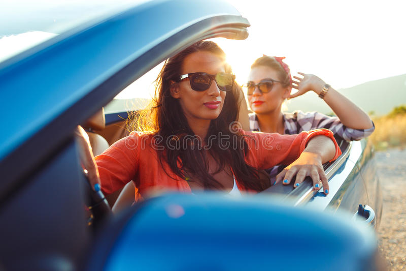 Two young girls driving a cabriolet stock photo
