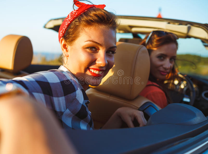 Two young girls driving a cabriolet stock photos
