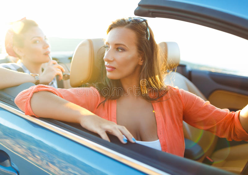 Two young girls driving a cabriolet stock image