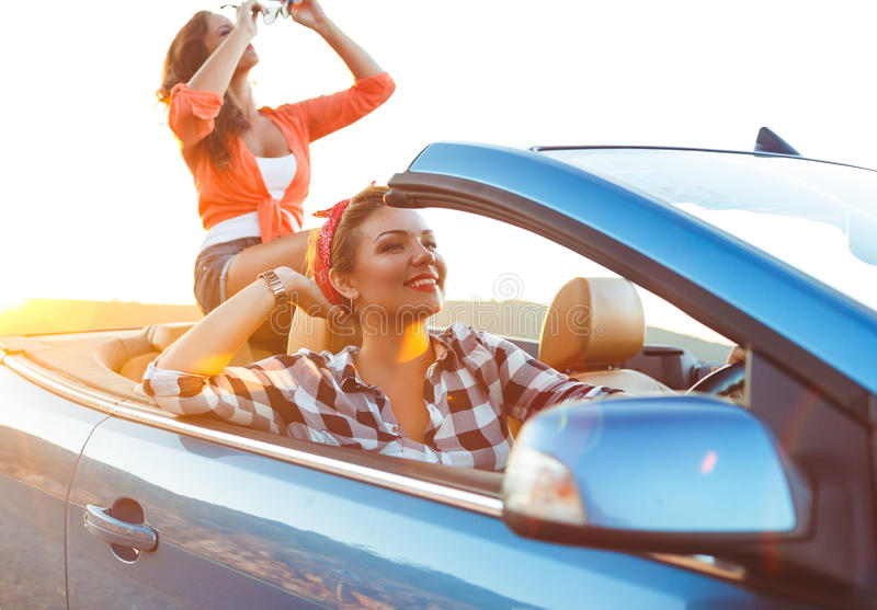 Two young girls driving a cabriolet royalty free stock image