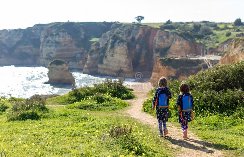 Two young girls exploring Portuguese coastline. Praia Dona Ana, Lagos, Algarve, Portugal stock images