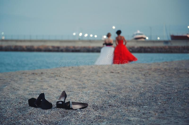 Two young girls in fashionable dresses walking at sandy beach without shoes evening time. Teens together outside at the beach stock photography