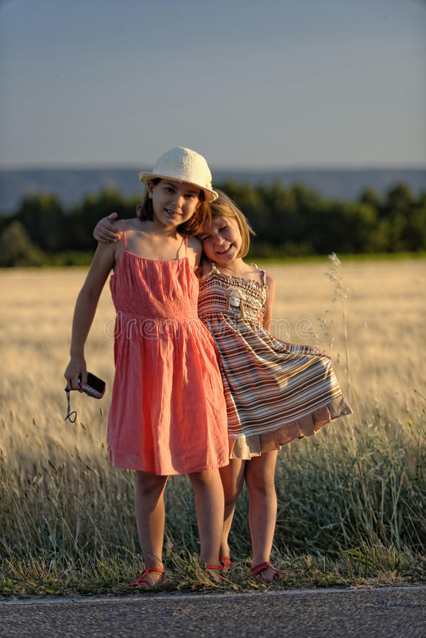 Two young girls in field stock photography