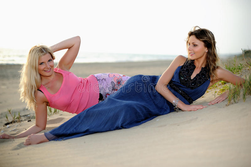 Two young girls friends relaxing on the beach stock image