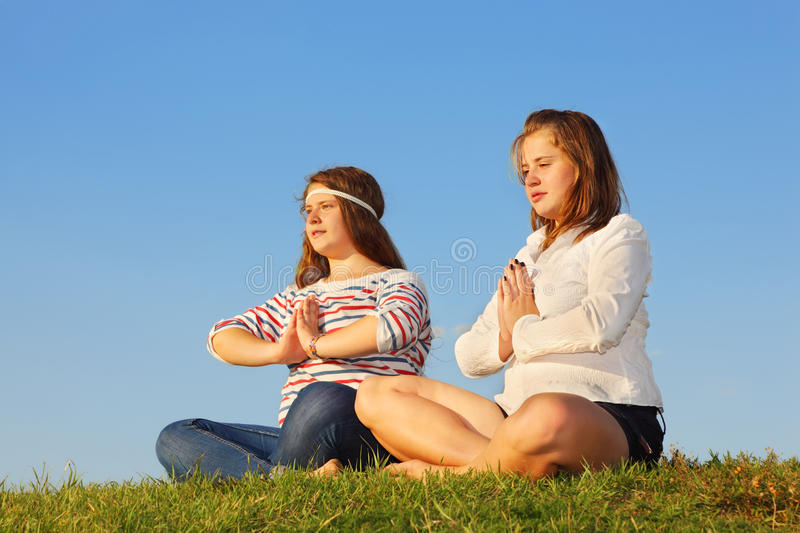 Two young girls meditate and reflect at grass stock photos
