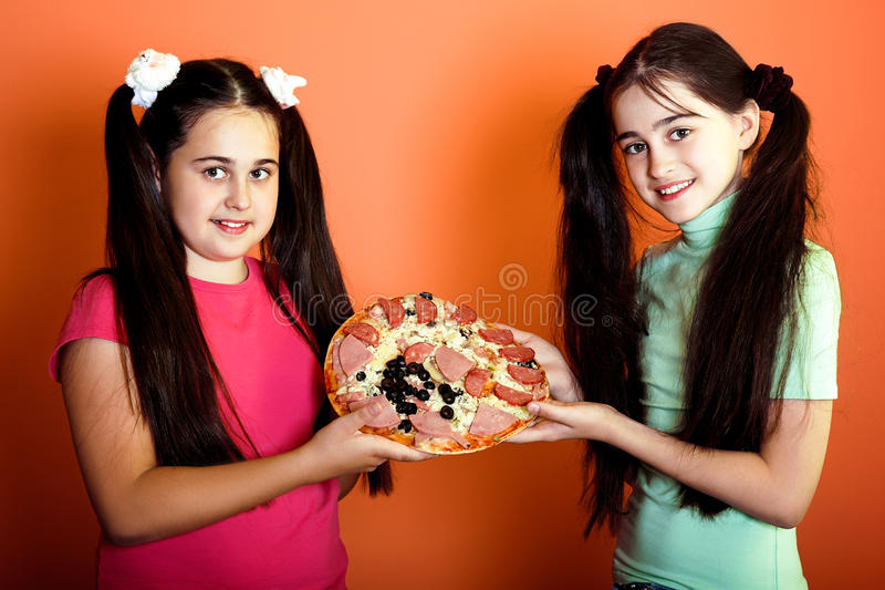 Two young girls with one pizza royalty free stock photos