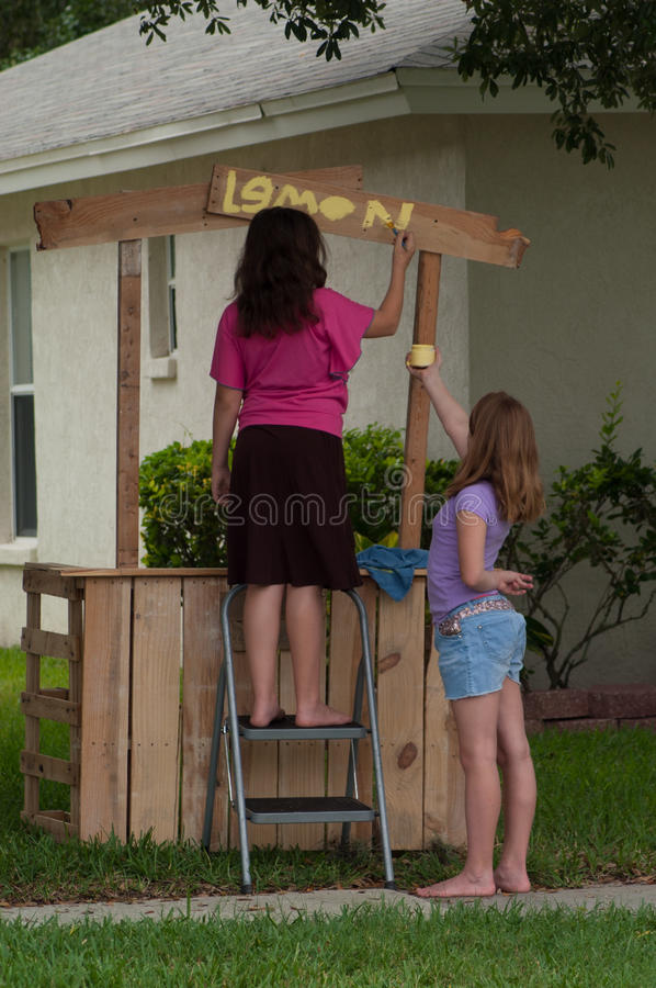 Two young girls painting a lemonade stand royalty free stock images