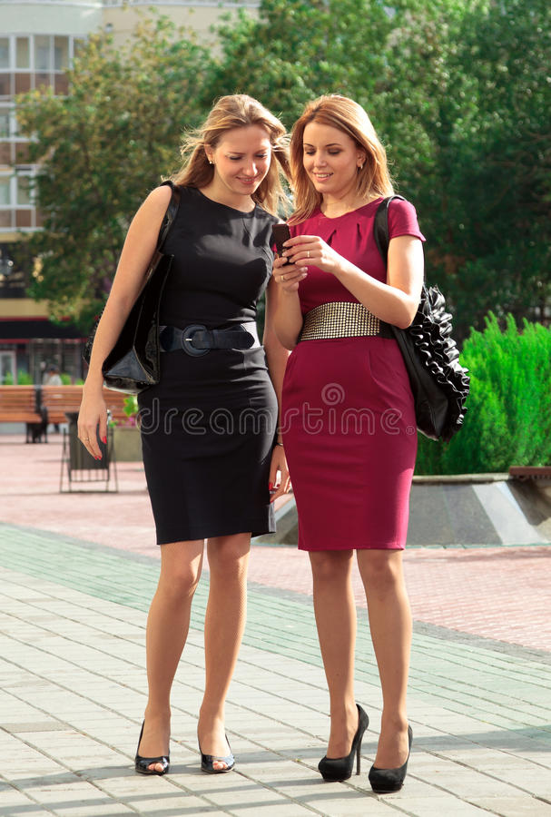 Two young girls with a phone stock images