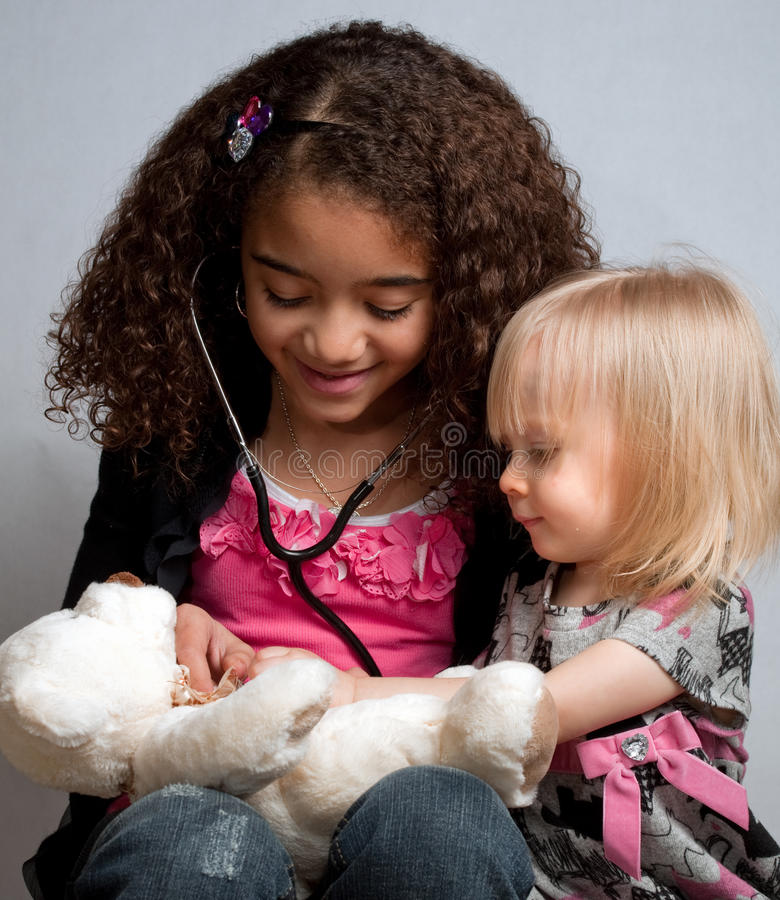 Two young girls playing doctor royalty free stock photo