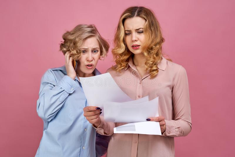 Two young girls pose for Studio portrait on isolated background. Negative emotions on face are caused by unpleasant news. royalty free stock image