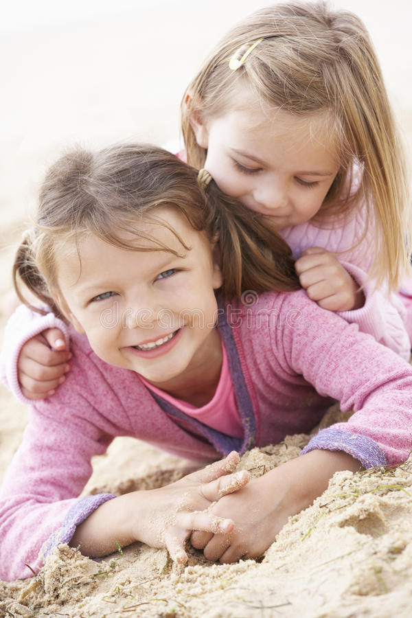 Two Young Girls Relaxing On Beach stock images