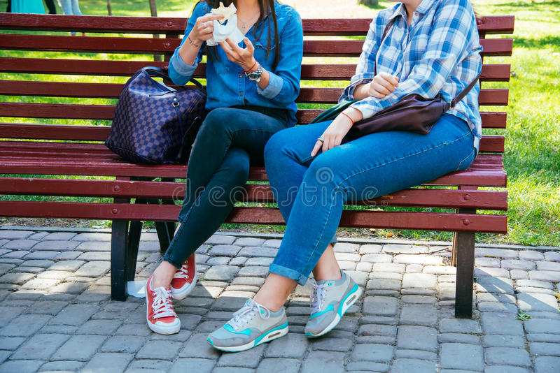 Two young girls sit on a bench Urban lifestyle. Two young girls sit on a bench. Urban lifestyle. Students have a rest in the park. Are dressed in jeans clothes stock photos