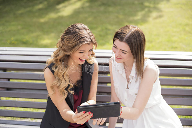 Two young girls sitting on a bench in a park watching the tablet and laughing royalty free stock image