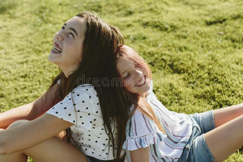 Two young girls sitting on the grass back to back laughing. Two teenage girls sitting back to back on the grass. They`re laughing. They have long hair. They`re royalty free stock photography