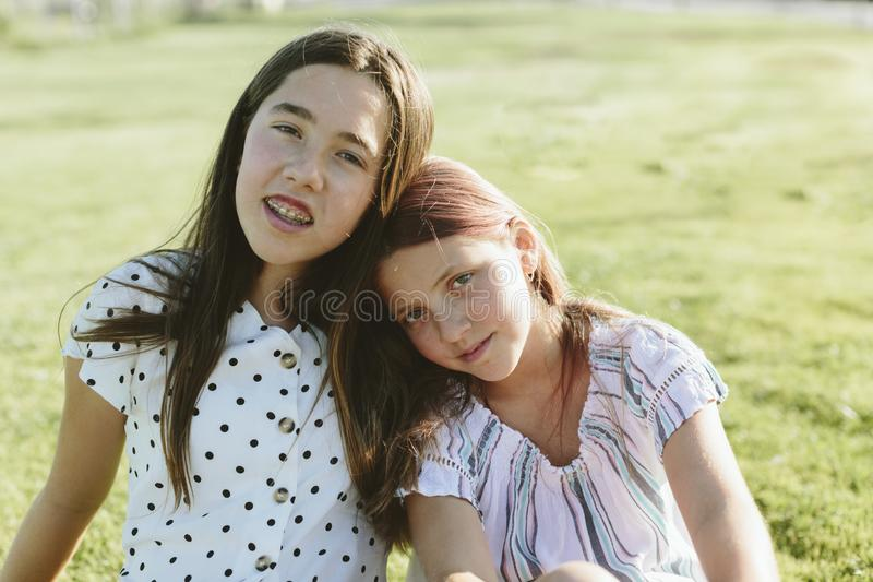 Two young girls sitting on the grass looking at the camera. Two teenage girls with heads together. They`re sitting on the grass. They have long hair. They`re royalty free stock image