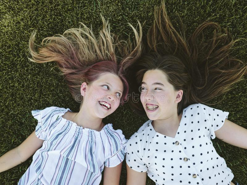 Two young girls sitting on the grass lying on the grass looking at each other. Two teenage girls lying down on the grass heads together. They have long hair stock images