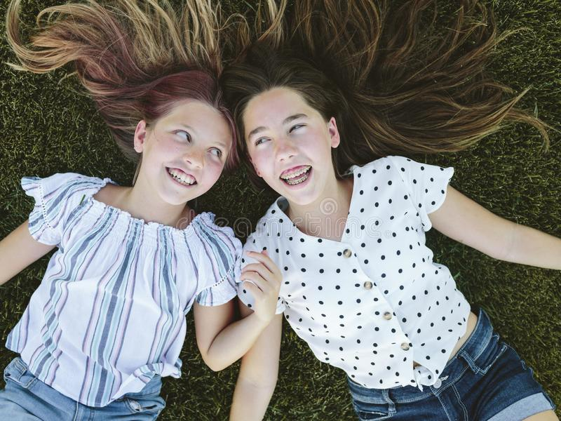 Two young girls sitting on the grass lying on the grass looking at each other. Two teenage girls lying down on the grass heads together. They have long hair royalty free stock image