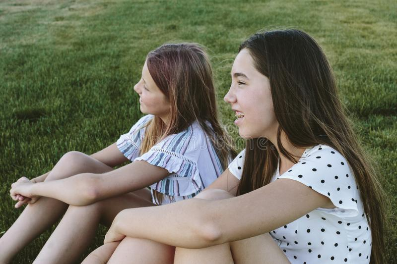 Two young girls sitting on the grass smiling looking to the left. Two teenage girls sitting next to each other on the grass. They have long hair. They`re wearing stock photography