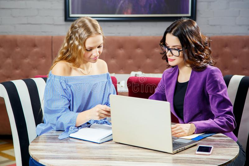 Two young girls sitting at the laptop while discussing business matters stock images