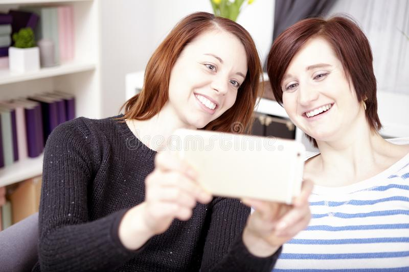 Two young girls with smart phone stock image