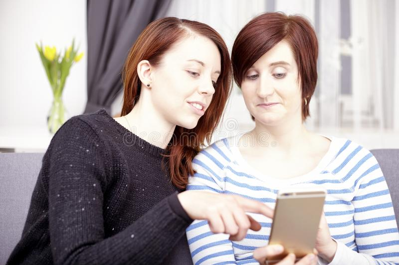 Two young girls with smart phone royalty free stock image