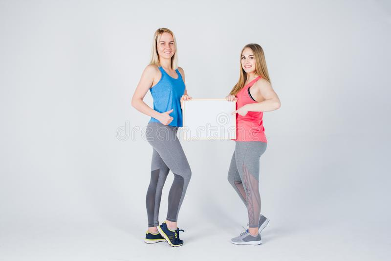 Two girls holding the frame with the ad stock photography