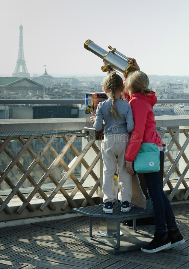 Two young girls stand up to the telescope attempting to gaze at the Eiffel Tower royalty free stock images