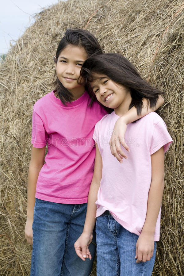 Two young girls standing by haybale royalty free stock photo