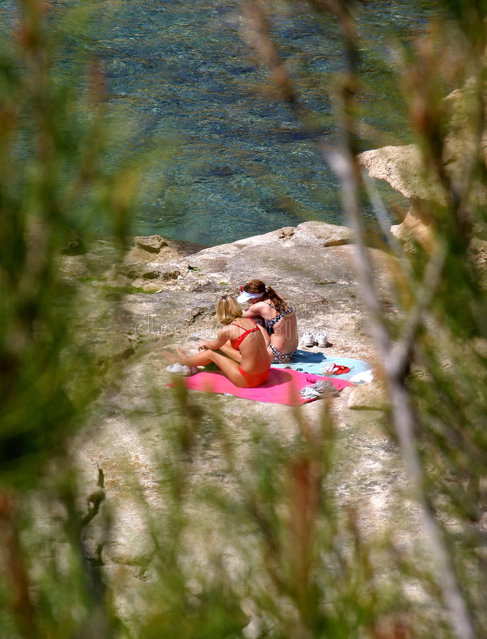 Two young girls sunbathing on rocks by the sea. Two young girls in bikinis sunbathing on rocks by the sea as seen through some bushes royalty free stock photos