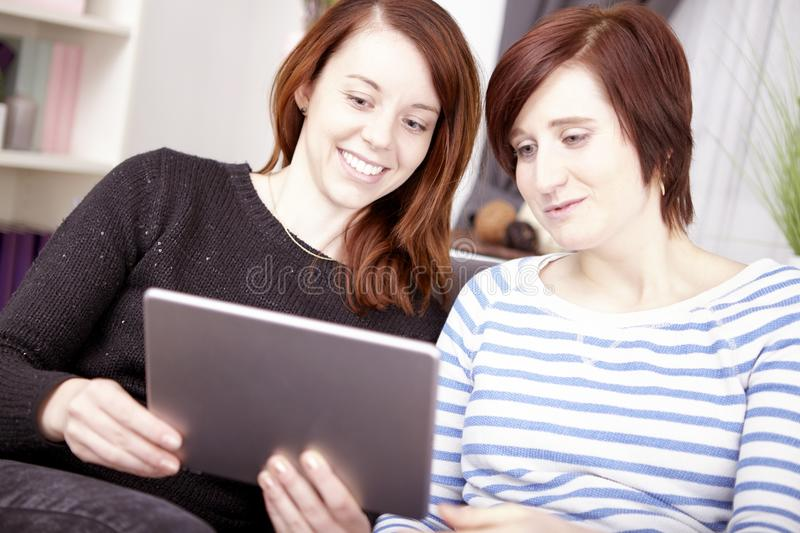 Two young girls with tablet computer stock image