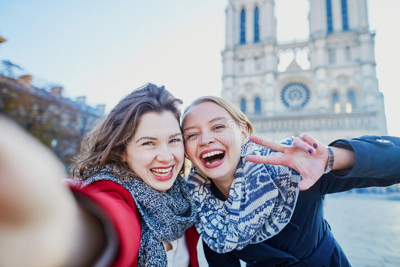 Two young girls taking selfie near Notre-Dame in Paris. Two young girls walking together in Paris taking selfie with mobile phone near Notre-Dame cathedral stock images