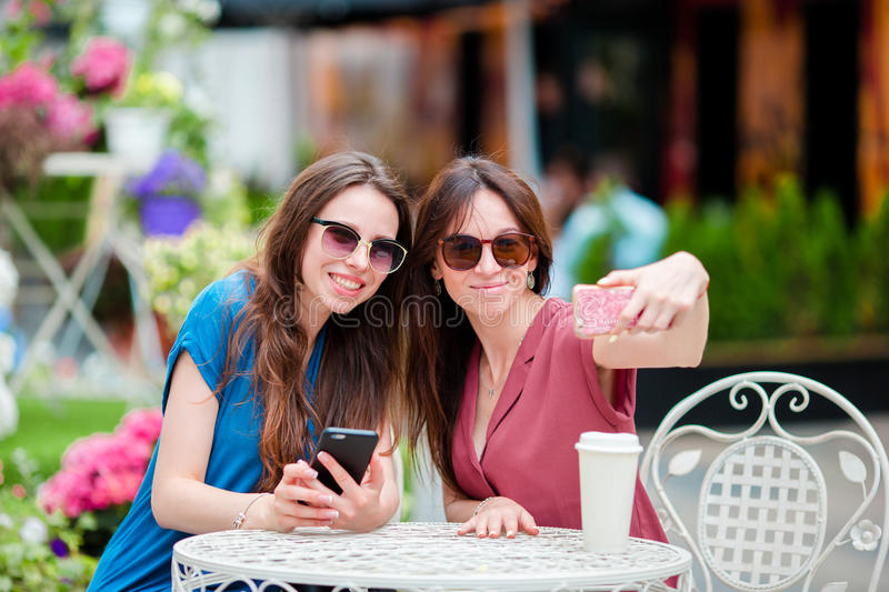 Two young girls taking selfie with smart phone at the outdoors cafe. Two women after shopping with bags sitting in royalty free stock image