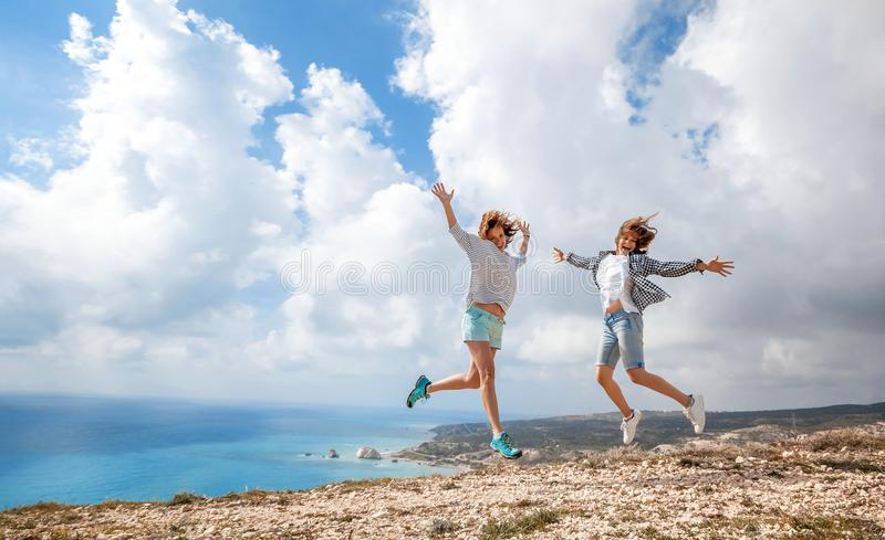 Two young girls traveler jumping against a stunning beautiful la royalty free stock photography