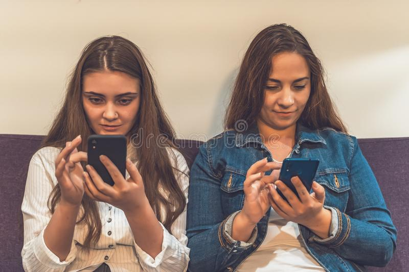 Two young girls use Social Media in their smartphones sitting together instead of talking to each other royalty free stock images