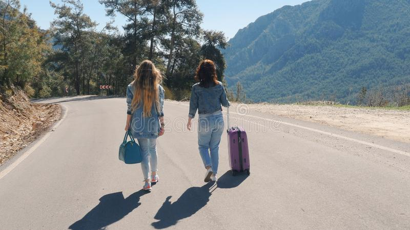 Two young girls walking down the road with beautiful nature landscape stock photo