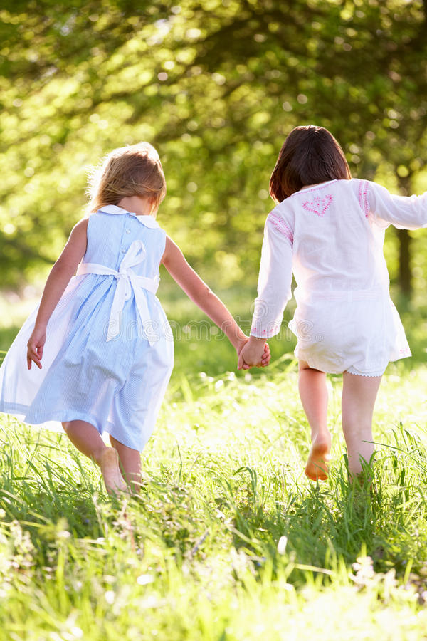 Two Young Girls Walking In Field Together