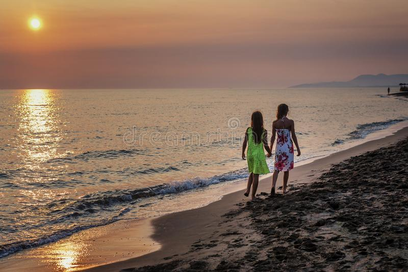 Two young girls walking together on the beach in the sunset.  stock image