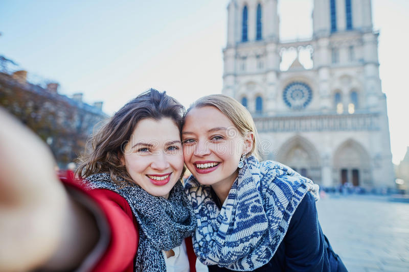 Two young girls taking selfie near Notre-Dame in Paris. Two young girls walking together in Paris taking selfie with mobile phone near Notre-Dame cathedral royalty free stock photos
