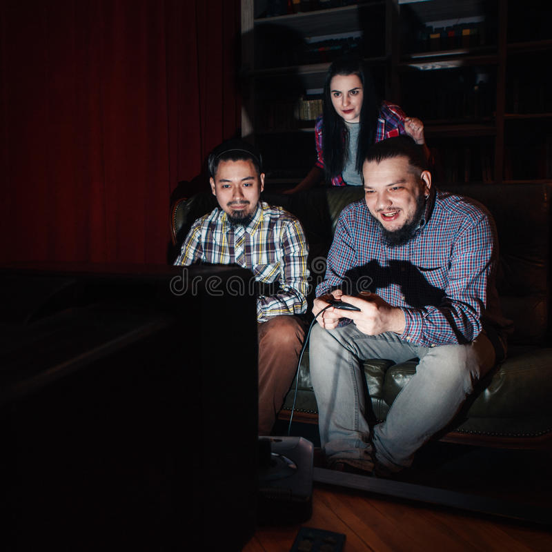 Two young guy play video game on couch, girl watch stock photo
