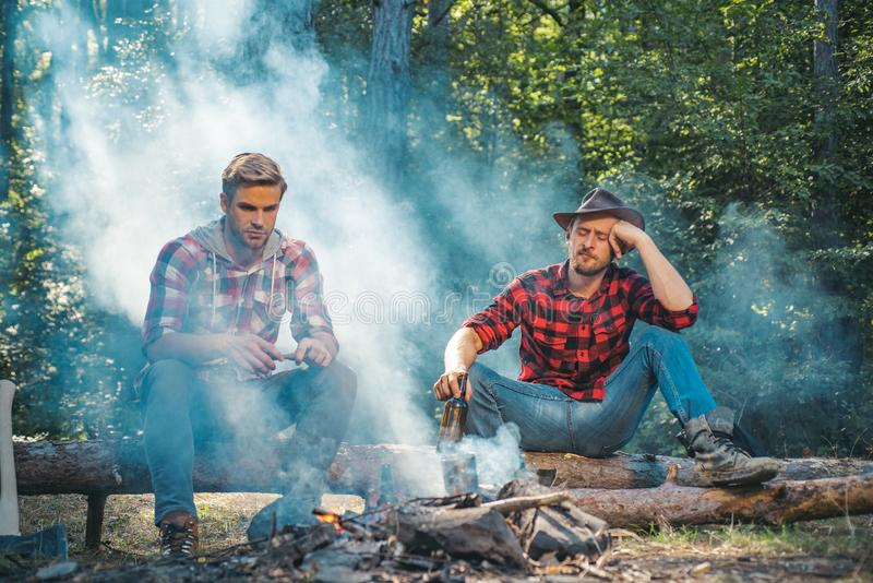 Two young guy sitting in the forest and drinking beer near campfire. Best friends spend leisure weekend hike barbecue stock photos